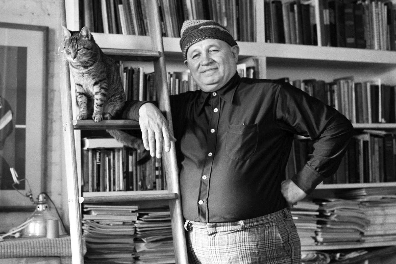 Romare Bearden portrait. Photo by Blaine Waller: Bearden stands in front of a wall of books resting on a ladder which also holds a cat. 1976