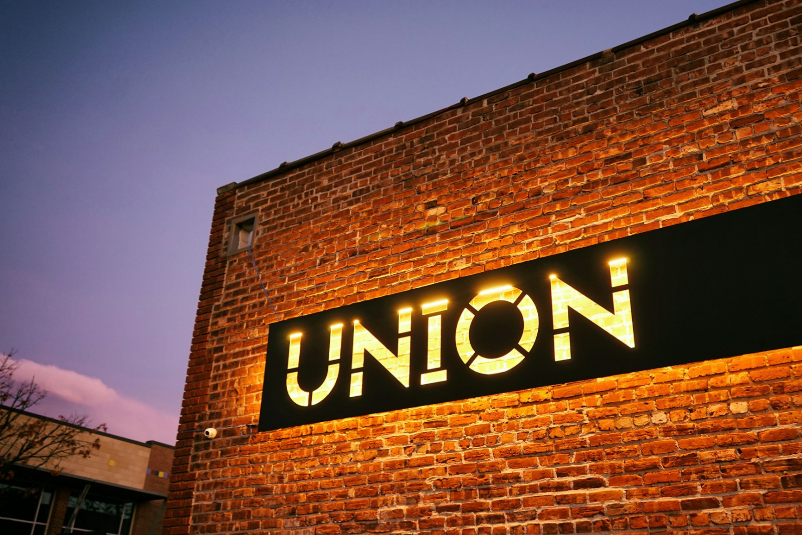 Union building at dusk A black steel Union sign hangs on a red brick wall and is illuminated with white light from behind