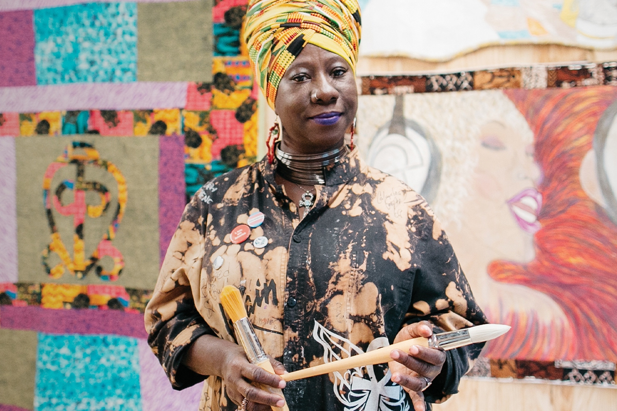 2017 Union Fellow Celeste Butler stands in front of two of her large quilts. She wears a yellow patterned head wrap and artist's smock, holding two paintbrushes. (Union program fellowship-1)